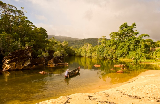 Malagasy man in a pirogue paddling in the Masoala National Park.